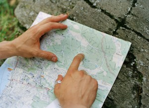 Man's hand pointing on street map