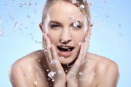 Young and beautiful woman washing her face