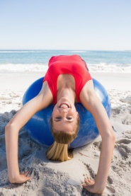 Fit blonde stretching back on exercise ball smiling at camera on the beach